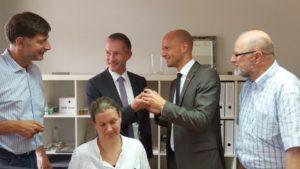 Volker Rosenberger (links) zeigt Stephen Paul, Ralph Bombis MdL und Siegfried Mühlenweg ein modelliertes Gebiss. Davor arbeitet Ulrike Twistel an einem 3D-Programm.